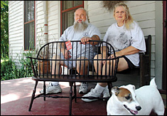 Ralph and Caron Quick — and their dog, Windsor — show off a child's settee made at the Windsor Chair Shop in Clarksville.